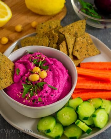 Beet Artichoke Hummus in small bowl on plate with vegetables