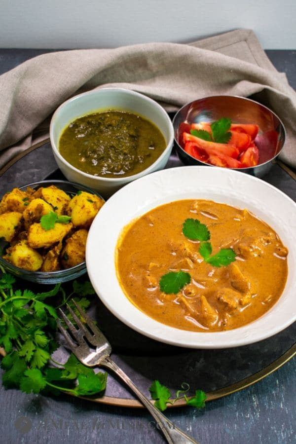 One-Pot Butter Chicken side view in white plate with side dishes