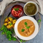 One-Pot Butter Chicken in white bowl with side dishes