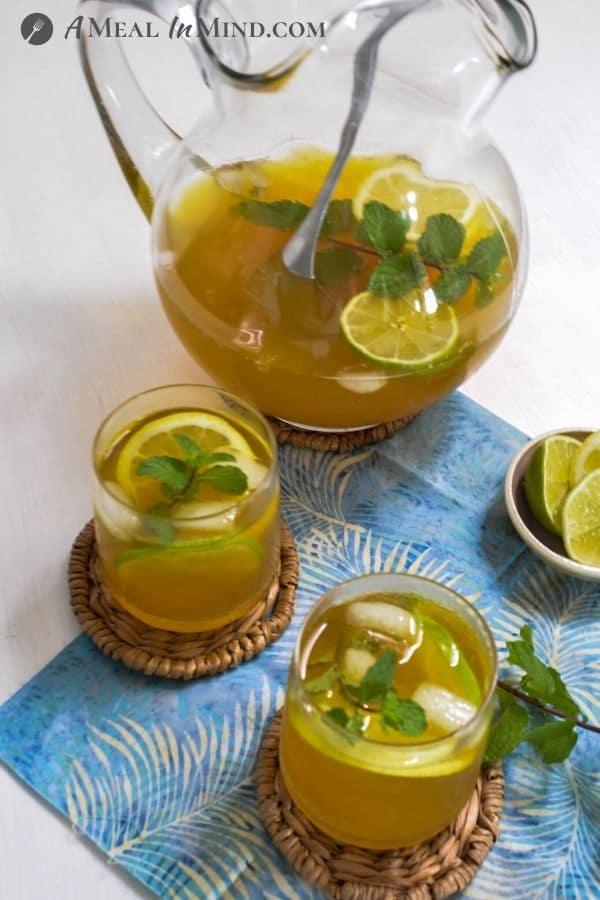 Turmeric-Ginger Lemon Tea glasses and pitcher on blue cloth