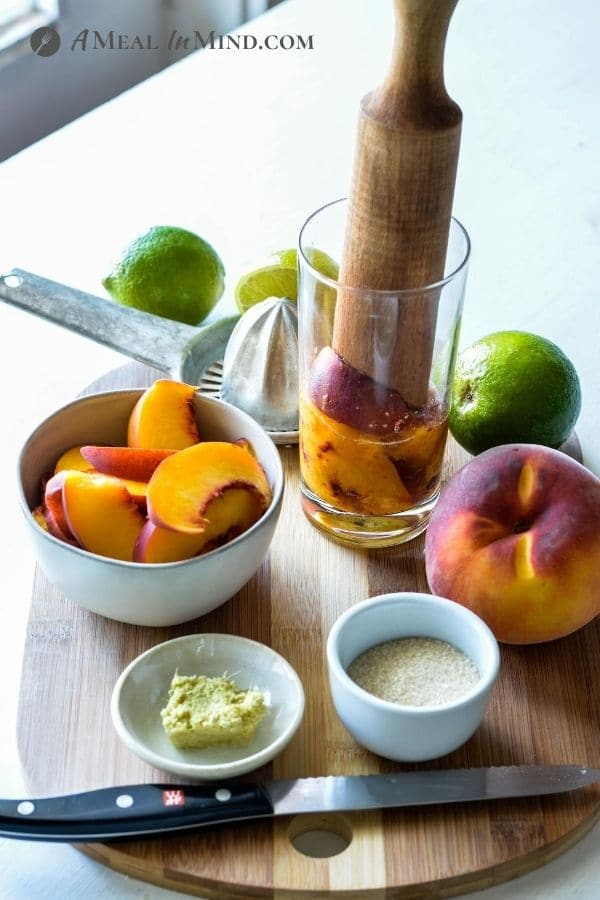 muddled peaches and other ingredients for Peach-Ginger Limeade Mocktail