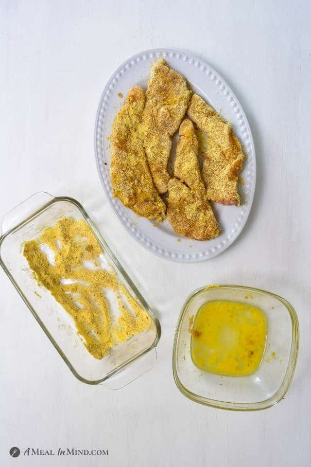 fish fillets on white platter after dipping in egg and seasoned corn meal