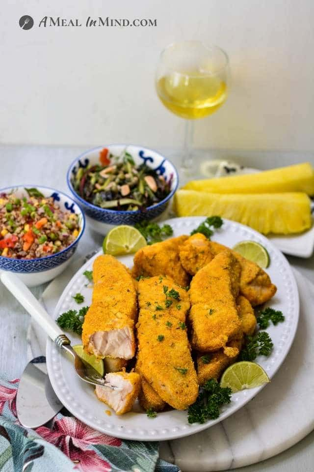 air fried opah on white platter with side dishes and wine glass