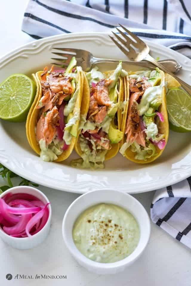 Parchment-Roasted Salmon Tacos with Yogurt-Avocado Crema on white platter