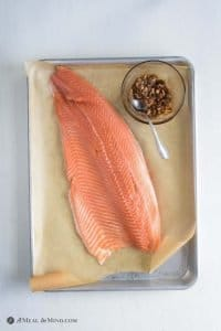 salmon and spice-garlic rub on parchment lined baking sheet