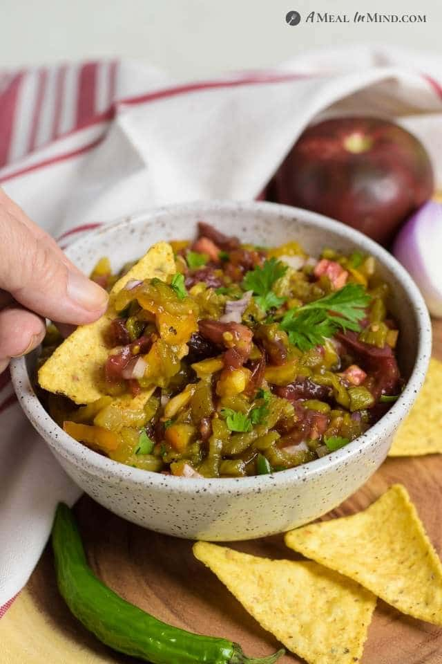 dipping a chip into Hatch Green Chile Heirloom Tomato Salsa