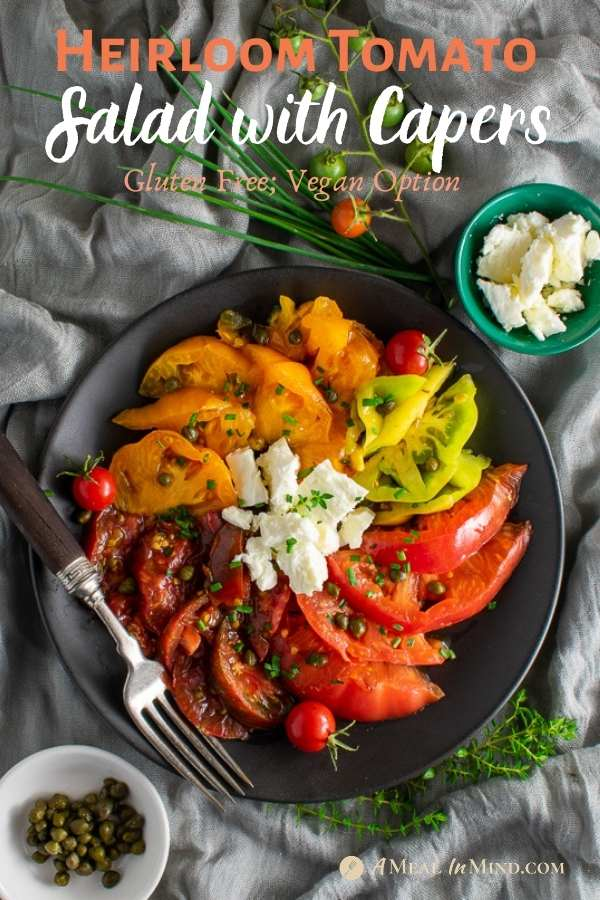 heirloom tomato salad with capers on black plate