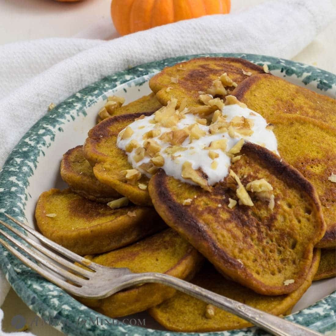 Pumpkin Protein Pancakes on ceramic platter with yogurt and walnuts