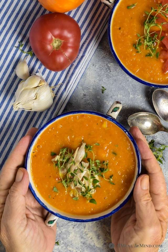 bowl of roasted butternut tomato soup in hands