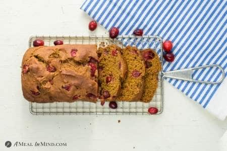 Cranberry pumpkin bread partly sliced on wire rack