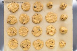 raisin oatmeal cookies being placed on baking sheet