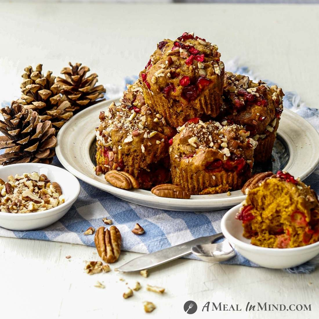 Cranberry-Pecan Pumpkin Muffins on ivory plate with scattered pecans