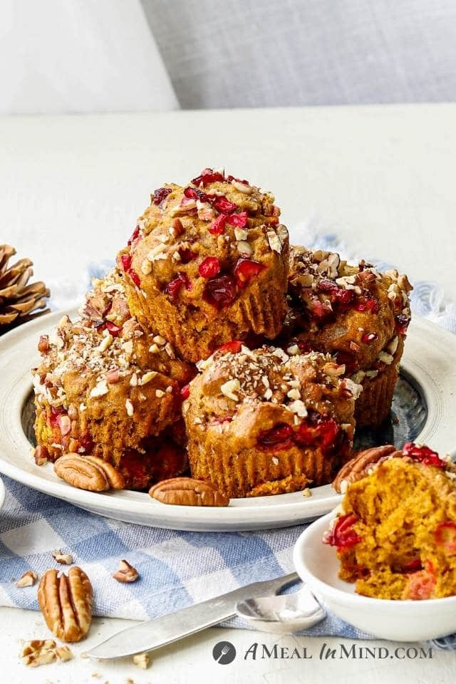 Cranberry-Pecan Pumpkin Muffins on plate with half muffin