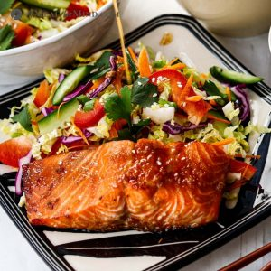 air fryer hoisin salmon on patterned plate with side dishes