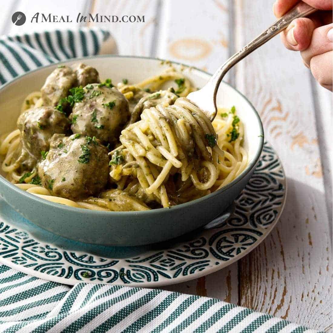 Paleo Pesto Meatballs and Alfredo Sauce in bowl on gf pasta